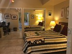 Private quest bedroom suite with queen bed and ceiling fan, flat screen TV, and work desk.