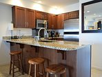Beautiful kitchen with granite countertops and bar seating.