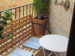 Balcon avec banc et petite table accessible depuis la salle de séjour