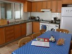 Kitchen with fridge/freezer, washing machine, dishwasher, microwave, toaster, kettle, coffee maker.