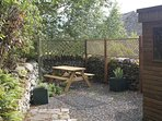 The private garden with lockable shed for storage, picnic table and herbs in pots.