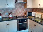 Kitchen has electric oven and gas hob