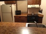 Kitchen features elec cooktop, vent, microwave, fridge, dishwasher and many small appliances.