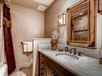 Guest Bedroom 3's en suite has a single sink vanity and shower/tub combo.
