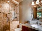 The en suite here has a walk-in shower and single sink vanity.