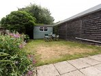 Lovely sun trap garden blessed with  sweet pea flowers and comfy  garden furniture
