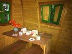 Kinder-Spielhaus liebevoll für Kinder eingerichtet mit Sitzbank und Küche