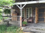 Partial porch view with barn door for entry door and old horse stall dividers for railings.