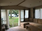 Spacious lounge with French doors looking onto woodland area.