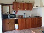 Kitchenette with tall fridge/freezer, microwave, worktop oven, 2 burner gas hob, cutlery/crockery.