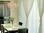 Sheer curtains create a wall of soft light that floods the dining area.