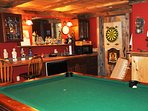 Billiard room features a wet bar, beer fridge, microwave, and dart board.