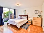 Bright master with new furniture & CalKing bed. Sliding door to side yard.  Hear the ocean!
