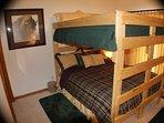 Buffalo room has queen bunk bed over queen bed with sliding glass door to patio