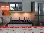 Cozinha completa com fogão, exaustor, micro-ondas e geladeira com freezer