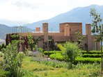 View of the villa set in the communal gardens with the Atlas Mountains in the distance