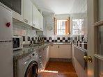 Main appliances include: fridge-freezer, microwave, vitroceramic stove, washing-machine-dryer.