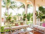 Breezy terrace surrounded by luscious green garden.