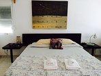 Dormitorio con cama king size y baño privado con vistas al jardín y la piscina