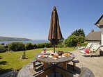 Gwbert holiday cottage - patio with views over the Teifi Estuary to Cemaes Head
