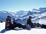 Snowboarders having a break in front of stunning view