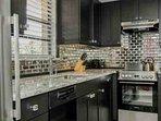 Enjoy this dream kitchen w/custom cabinets, quartz counter tops, & unique mirrored subway tile backsplash