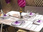 Moment convivial : repas en extérieur sur la terrasse intime protégée du soleil par un voile.