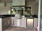 Outdoor kitchen. Fridge, rotisserie and BBQ.