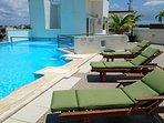 vista piscina con camastros para el relax