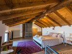 the master bedroom with wooden roof beams