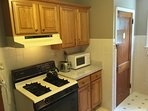 Kitchen Stove, Toaster & Microwave. Stairs to Basement with Washer & Dryer