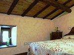 ...soffitto perlinato, con travi di legno e comodino restaurato.