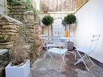 The small, pretty courtyard, with a table and four chairs