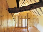A low oak beam crosses the entrance to the eaves bedroom