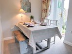 Dining table for four, with French doors leading to the garden