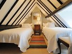 The charming twin bedroom in the eaves, filled with character
