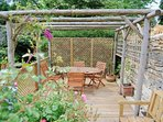 The raised decking area with table, chairs and a BBQ
