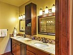 The en-suite master bath features his-and-hers sinks with lavish finishes.