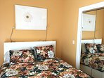 Yellow bedroom on the second floor with mirrored closet; quin bed, 100% cotton quilt, original art