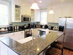 Fully equipped kitchen boasts stainless steel appliances and granite countertops with bar seating