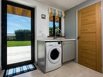 Utility room with washing machine and separate tumble dryer. Iron and ironing board.