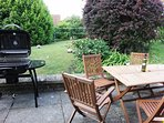 Large garden with patio furniture and BBQ.