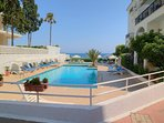 Neat area with two swimming pools and sunbeds with sun umbrellas right next to the sea!