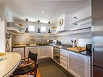 Bright kitchen equipped with gas stove, oven, microwave, dishwasher, electric juicer, toaster,...