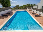 Large communal swimming pool with sea view and private sunbeds