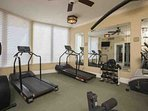 A variety of work-out machines in fitness room with T.V.