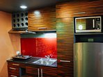 Our kitchen with microwave oven, fridge, rice cooker, electric stove and exhaust.