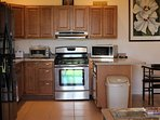 Full kitchen with stove, microwave, silverware, glasses