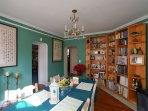 A large bookcase, full of original artwork and reading material from around the world