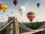 With a wind from the SW balloons float over the city - here passing the Clifton Suspension bridge
